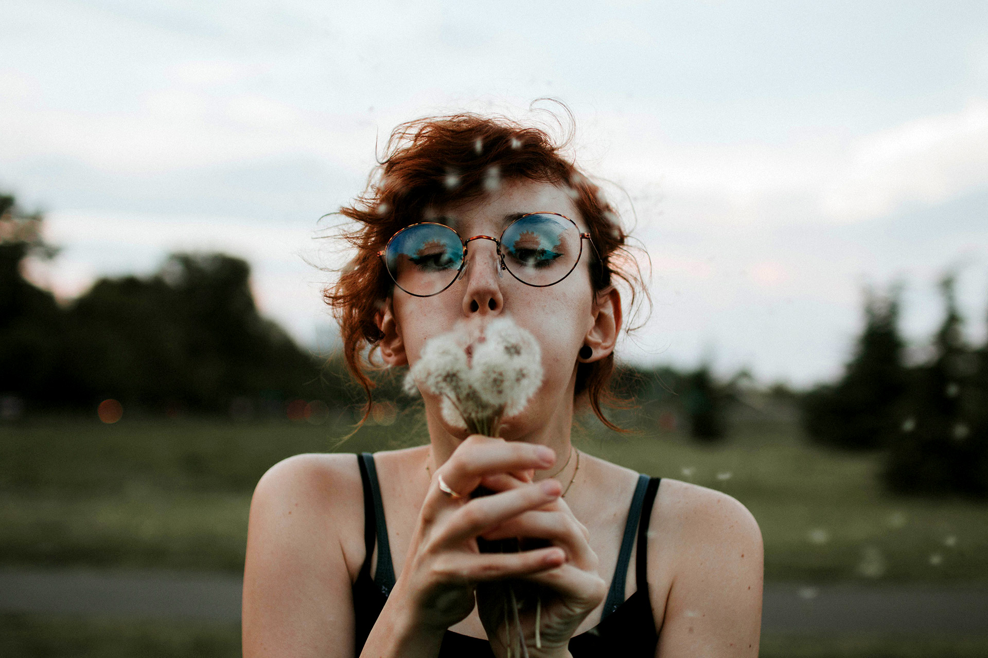 Girl blowing on dandelions in a park